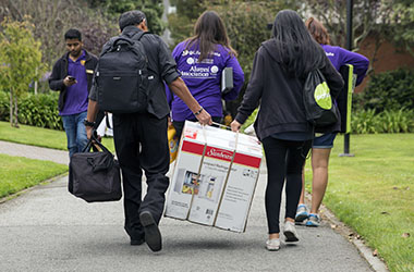 Student walking with move-in boxes